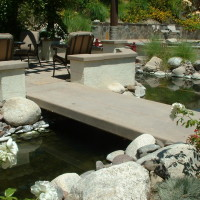 Concrete bridge spans the koi pond to the BBq and fireplace dining area.