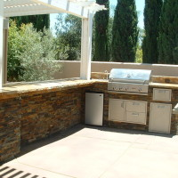 Counter bar/ BBQ island with granite counter top, stacked quartz ledger panel sides.