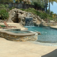 Artificial rock waterslide and walk-in cave/grotto. Spa has stacked high desert vaneer with poured in place colored concrete coping. Tahoe blue pebble finish, quartz beach entry.