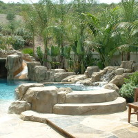Raised spa with artificial rock steps and boulders, beach entry, baja.
