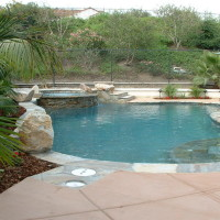 Freeform pool with natural boulder accents, quartz on baja, stacked quartz spa spill wall. Quartz coping and tile.
