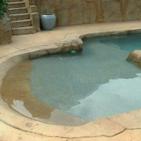 Beach entry and baja landing added to an existing rectangle pool with Rock textured concrete coping and Tiger eye lagoon pebble by Gemstone.