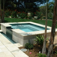 "18"" Raised spa with Travertine coping and glass tile. Description 	: 	Double bull nosed travertine and Oceanside Glass tile with a spillway into a separate catch basin. Homeowners can see the waterfall from the spa while the auto cover warms the pool. 24"" walk-on lid trays to hide the auto cover in front of spa."