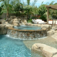 Diablo quartzite stacked spa spill wall and artificial rock waterfalls. Beach entry and baja jetty boulder.