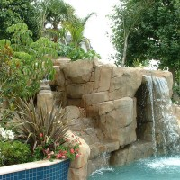 Artificial rock waterslide, grotto, and waterfall with a blend of tropical/mediterranean landscape. Description : Tropical Oasis
