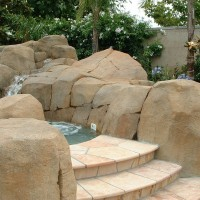 Artificial rock boulders and waterfall surround raised spa. Arizon flagstone deck steps.