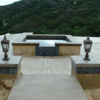 Raised spa spills into a seprate catch basin so the homeowners can see the waterfall from the house.