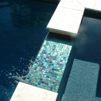 Oceanside glass tile spa spillway with travertine coping. Polished pebble aggregate by Wet Edge technologies, Inc.
