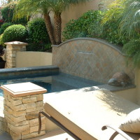 Water feature with shear decent on this spa design. Tropical landscape is always a nice touch.