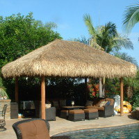 Inviting outdoor living area with poured in place colored concrete and palapa.