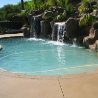 This pool is a remodel. The kidney shaped pool with white safety coping and gray concrete decking.