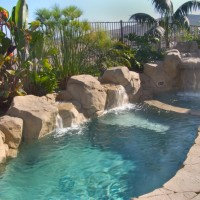 Special features: Artificial rock waterfalls and boulders, coping and tile. 8' x 16'x 5' deep splash pool with baja landing and seperate spa. Pebble tec, color changing lights, salt water pool, lush tropical landscaping. San Clemente, Ca. Description : Artificial/Simulated Rock Splash Pool in a small package
