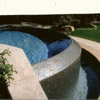 Special features: Oceanside glass tile on a o-edge infinity pool spill wall and catch basin. Natural travertine coping. Slate and travertine banded decking. Description : Negative edge/ infinity spillwall with Oceanside glass tile