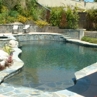 Freeform pool and spa blended into the surroundings. Quartzite beach entry with pebble tec.