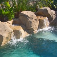 Artificial rock water feature with boulders and cascading falls. Attached spa and spa controls mounted in rock.