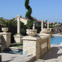 Fire bowls and planting pots accent these (4) columns.