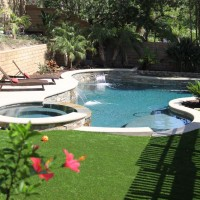 Natural freeform pool and spa with artificial turf bordering the poured in place colored concrete coping.