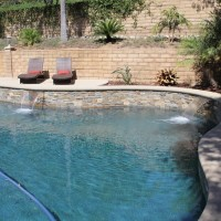 Stacked quartz raised wall and quartzite waterline tile accent the natural pool design.