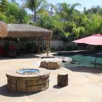 Fire pit, umbrella in pool baja landing. Palapa shade awnings on house match palapa and provide for shade without posts.