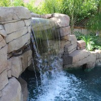Artificial rock waterfall with walk-in grotto/ cave. Rocks are hand carved and rock textured before acid staining to create a natural look.