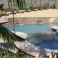 Raised pool wall with stacked quartz ledger panels and shear decent waterfalls.