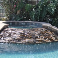 Custom raised spa with angled stacked quartz waterfall.