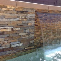 Custom raised spa wall with 4' shear decent waterfall, Oceanside glass tile, and stacked quartz veneer.