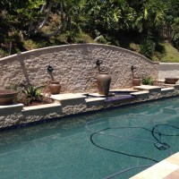 5' Stone wall with travertine coping, stone veneer, Bobe canon's and water urns, fire bowls, planter boxes, and lighting.