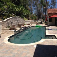 Travertine pool and spa coping, Belgard paver decking, custom Spanish style tile, dark mini pebble.