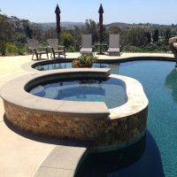 Colored concrete with sand finish bands the pool and spa.