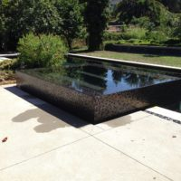 Glass tiles accent this complete overflow spa design.