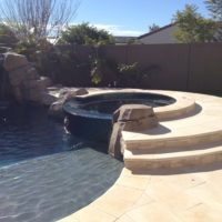 Raised level spa with glass tile spillway. Manmade rock accents.