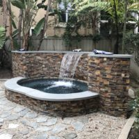 Spa with raised accent stone wall. Small yards can still be exiting.